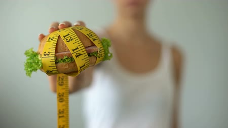 overweight : Girl holding hamburger wrapped in measuring tape, junk food, unhealthy lifestyle