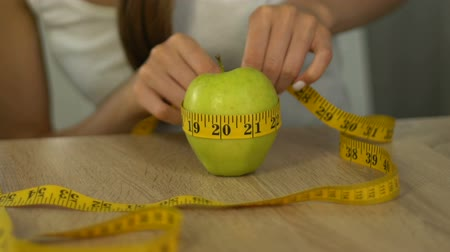 female measurements : Woman measuring apple with tape-line, calculating calories, body mass index