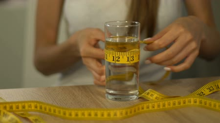 fobi : Woman measuring glass of water with tape-line, obsessed about calories, anorexia