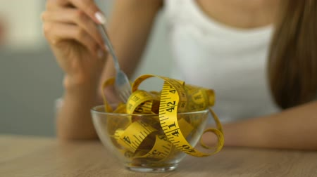 bulimia : Anorexic girl eating measuring tape, concept of dependence on calorie counting Stock Footage