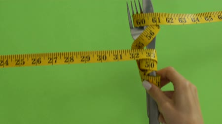 сантиметр : Cutlery tied with measuring tape, strict food restriction, calories calculations Стоковые видеозаписи