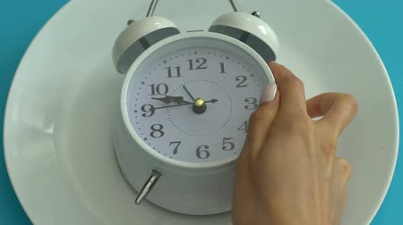 dietético : Alarm clock on empty plate, healthy diet schedule, daily nutrition, closeup Stock Footage