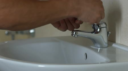sanitize : Scrupulous man wiping tap with napkin, lover of cleanliness, fear of germs