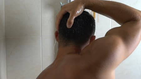 graxa : Back view of man thoroughly washing greasy hair, suffering from dandruff