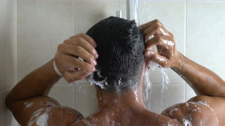chuveiro : Man taking shower in small bath cabin of cheap hotel, business trip, low-budget