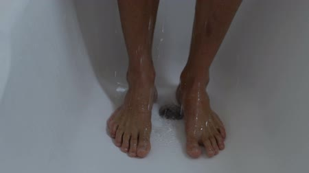 barefooted : Man standing in public shower with bare feet, hygiene. Stock Footage