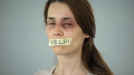 tyranny : Woman with help sign on taped lips, helpless victim begging for support