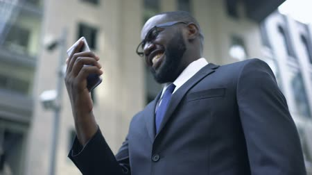 afro amerikai : Businessman happy to win money, using smartphone for bets and trading online