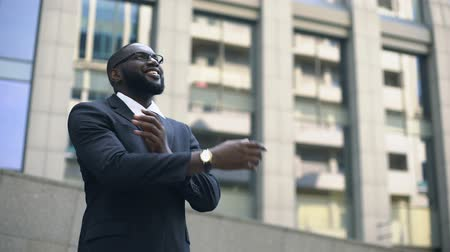 self motivated : Afro-american man in suit looks up into bright future, motivated for success