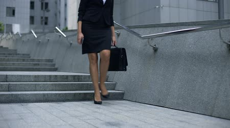 модный : Lady in business suit walking downstairs from office center, end of working day