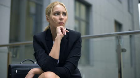 licenziamento : Anxious woman sitting on bench, worried about dismissal from work, depression