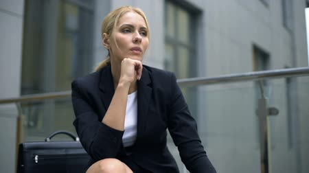 licenziamento : Pensive businesswoman sitting on bench, worried about troubles at work.