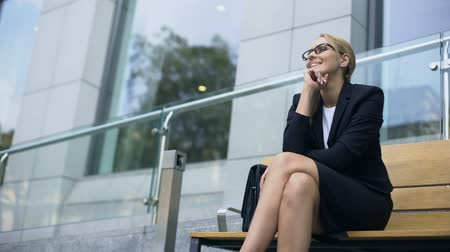 self motivated : Female entrepreneur sitting on bench, smiling, rejoicing at successful day Stock Footage