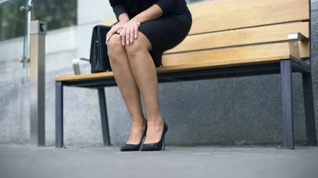 high heeled shoe : Woman sits down on bench, tired of walking in uncomfortable high-heeled shoes