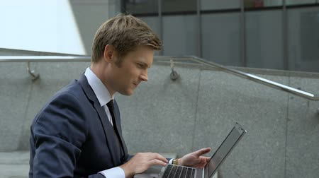 wi fi : Lucky businessman using laptop to check stock market, sitting on stairs outdoors Vídeos