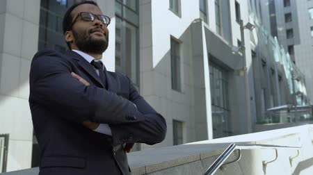 self promotion : African american businessman standing near office building, optimistic outlook
