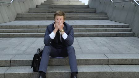 Ко : Upset man sitting on stairs, lost money on stock market, bankruptcy.
