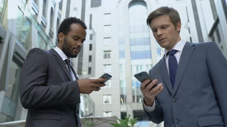 cortes : Two businessmen using smartphones, exchanging contacts, profitable acquaintance Vídeos