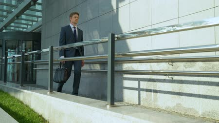 büszke : Handsome man leaving office building, end of working day, business people Stock mozgókép