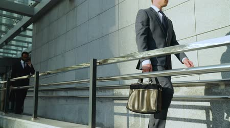 attorney : Business people leaving office building after successful working day, routine