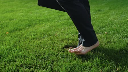 lehkost : Man walks barefoot on lawn, relax after difficult day, dreams about holiday