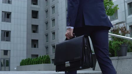 on the go : Successful male politician going upstairs with briefcase and phone, businessman