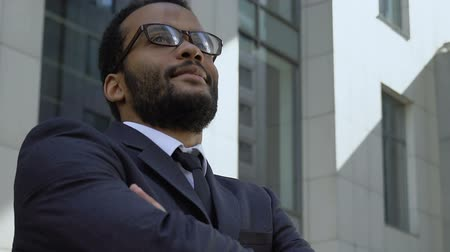 self promotion : Successful afro-american businessman standing near office building, closeup Stock Footage