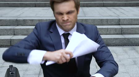 zuřivý : Businessman reading report, angry about project failure, throwing out papers