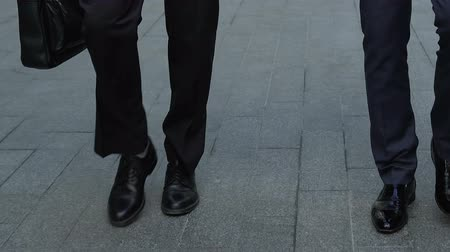 texte de loi : Two businessmen walking outdoors, executives going to meeting, legs closeup