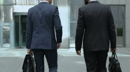 законодательство : Real estate agents walking to office building, discussing contract, partnership