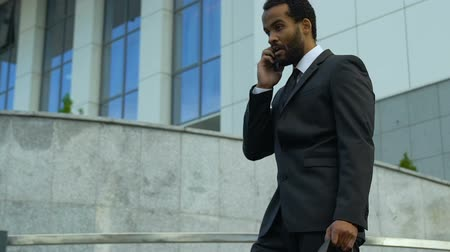 etyka : Afro-american businessman shouting in phone, stressed with deadline, overworked
