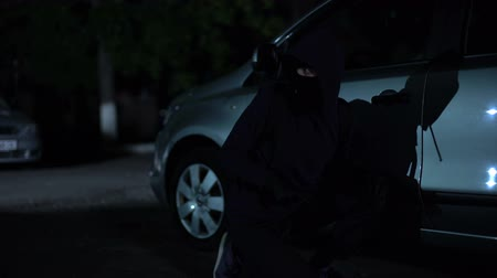property theft : Male criminal trying open auto on parking at night, carjacking, private property