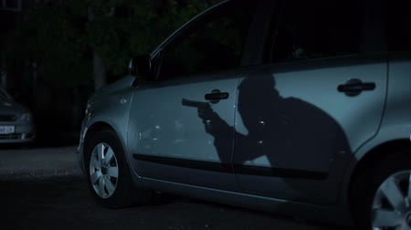 property theft : Shadow of gangster with gun walking on dark parking night, high-crime city area