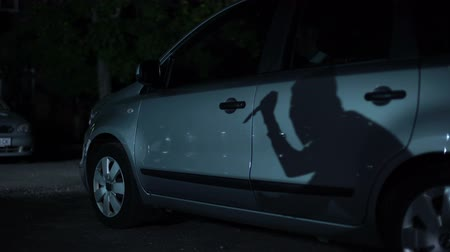гангстер : Criminal shadow with knife in hand reflecting on parked car surface, carjacking