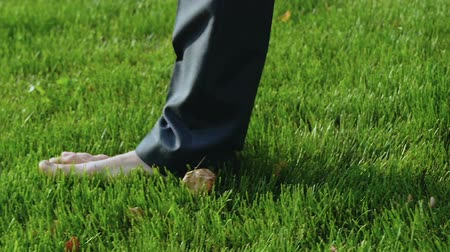 hafifletmek : Man in suit walks barefoot on lawn, office worker relaxing after work. Stok Video
