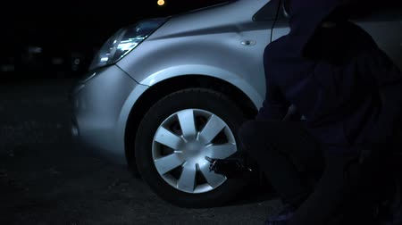 balaclava : Young criminal taking car wheel off at night, hooligan damaging property