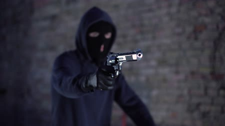 pistolero : Armed hooligan in mask extorting money from stranger, urban criminal activity