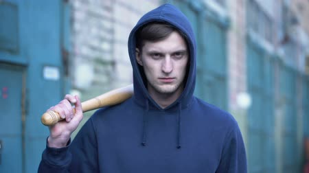quadrilha : Angry hooded bandit holding bat, getting ready for fight, criminal youth, attack Stock Footage