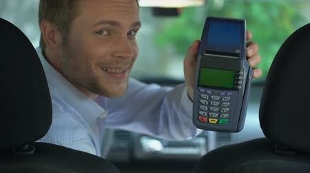 передавать : Handsome taxi driver showing payment terminal, contactless transaction service