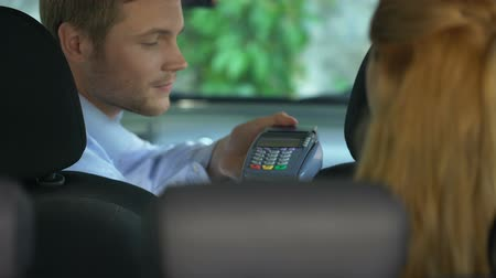 transmitir : Female taxi passenger paying contactless by credit card terminal, transaction