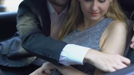 engedély : Pretty lady refusing boss harassment in auto, flirting man fastening safety belt
