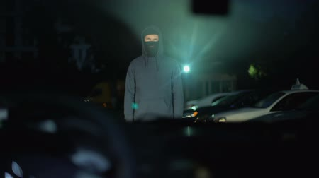 psycho : Dangerous criminal in balaclava standing in front of car, contract killing Stock Footage