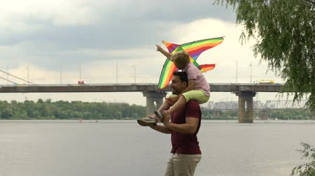 omzunda : Father and son launching kite near river, happy time together, parents love Stok Video