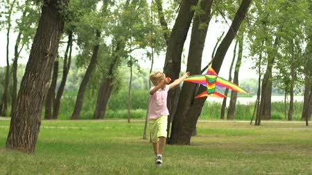 коршун : Boy launching kite in park, memories from childhood, happiness inspiration