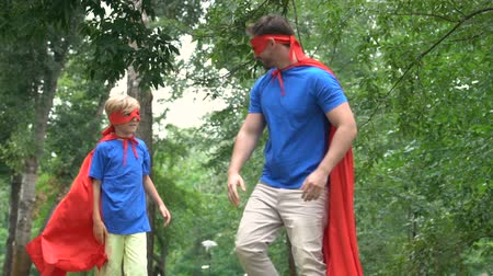 герой : Father and son in superhero costumes high-five, teamwork concept, goal achieving