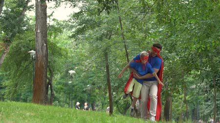 şaka : Son and father dressed in superheroes, playing together in park. Stok Video