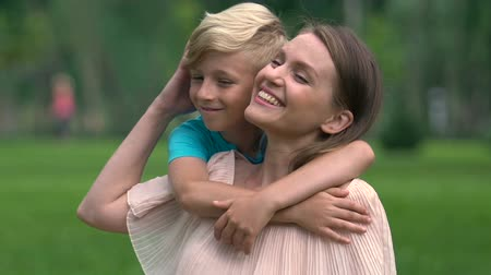 сестры : Single mother sitting in park and embracing son, spending leisure time together