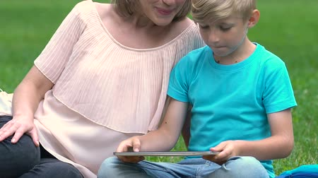 tab : Pregnant mum playing game on tablet with son, happy motherhood, family planning