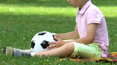 umutlu : Lonely boy sitting in park with ball, no friends to play with, bullying problem Stok Video