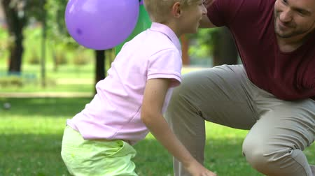 bóia : Loving parents congratulating little boy on birthday, outdoor party in park Stock Footage